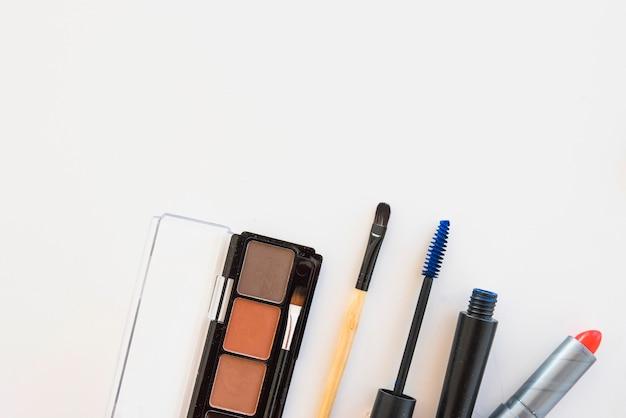 Palette d'ombres à paupières; brosse; rouge à lèvres et mascara sur fond blanc