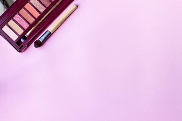 Palette d'ombres à paupières colorées dans des couleurs roses et un pinceau de maquillage sur un fond de papier rose, lilas avec espace de copie. palette de couleurs professionnelle pour le maquillage des yeux avec des ombres mates et chatoyantes