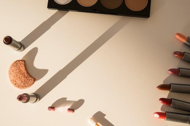 Palette d'ombres à paupières; éponge de maquillage; et variété de nuances de rouge à lèvres sur fond blanc