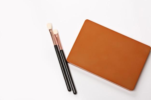 Palette d'ombres à paupières fermée avec pinceaux de maquillage sur fond blanc. espace pour le texte