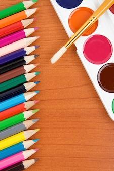 Palette de peintres avec pinceau et crayons colorés