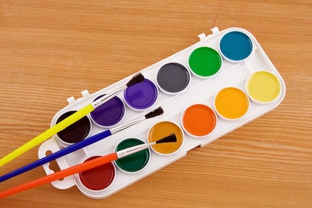 Palette de peintres avec pinceau sur la texture en bois