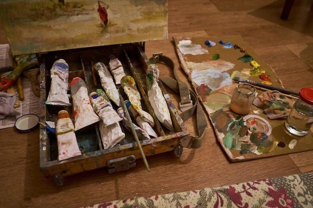 Palette de peinture avec un pinceau dans la boîte dans l'atelier de l'artiste