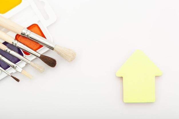 Palette de peinture avec pompons autocollants maison sur fond blanc. nouvelle vie et peinture du concept de maison