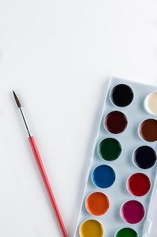 Palette avec des peintures à l'aquarelle et pinceau avec espace copie isolé sur whtie