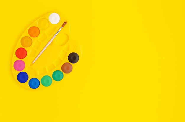 Palette de peintures aquarelles sur fond jaune. copiez l'espace, vue de dessus.