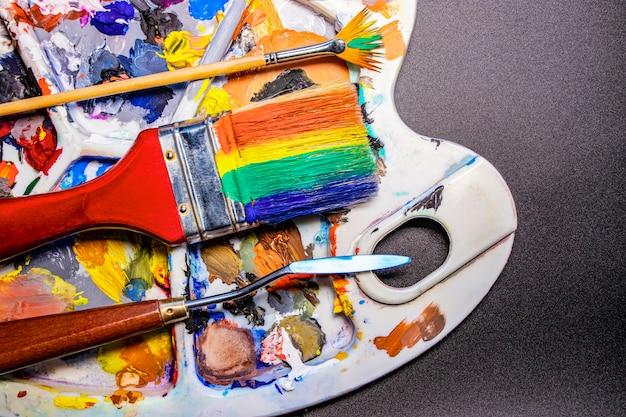 Une palette de peintures multicolores avec des pinceaux et un couteau à palette. fond noir. créativité et dessin. couleurs décalées.