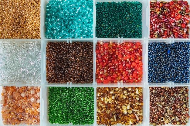Palette de perles de couleurs dans la boîte en plastique close up flat lay