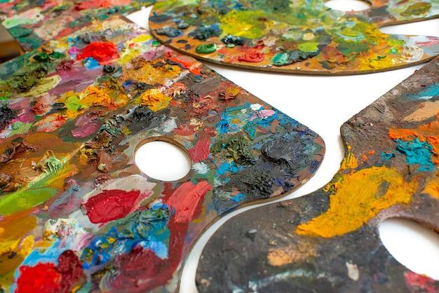 Palettes en bois colorées de peintures à l'huile d'artiste sur fond blanc. atelier d'artiste