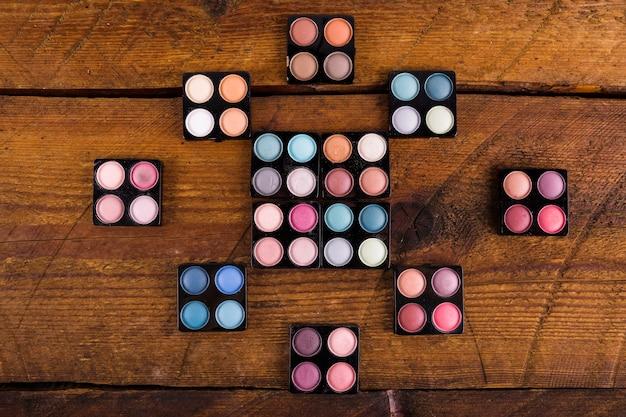 Palettes de diverses poudres colorées ombre à paupières sur fond en bois