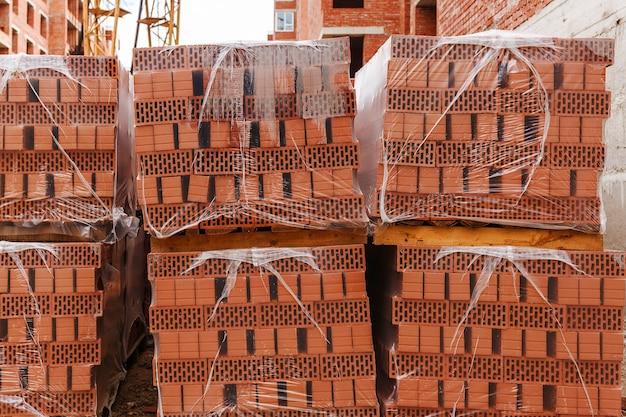 Palettes et paquets de briques rouges fraîchement produites dans un entrepôt de construction sur chantier