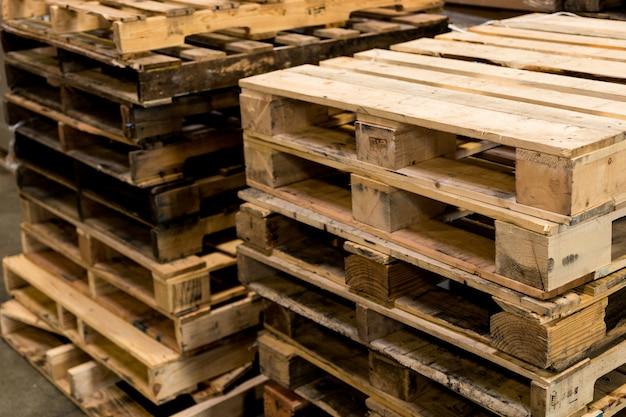 Palettes usagées et neuves empilées en rangées recadrées