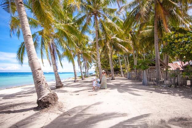 Palmeraie sur la plage de sable tropicale avec une famille de trois
