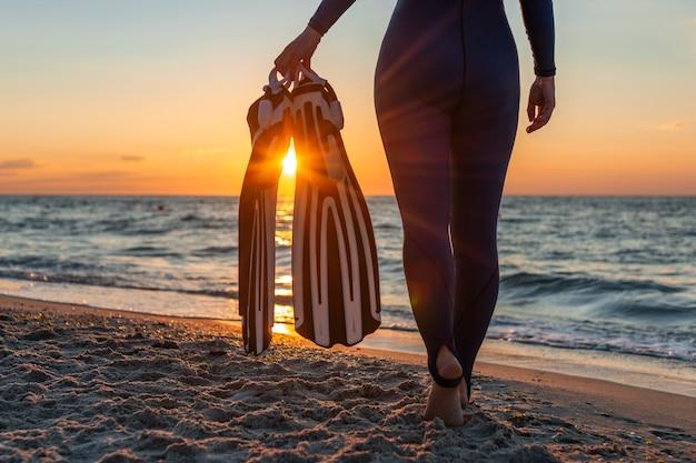 Palmes dans les rayons du coucher du soleil dans la main de la fille plongeur