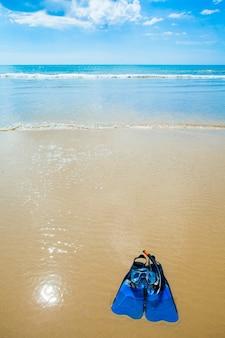 Palmes de natation, masque, tuba, chapeau dans les vagues sur la plage de sable
