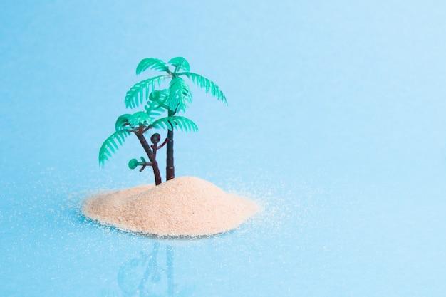 Palmier en plastique miniature dans le sable sur une surface bleue