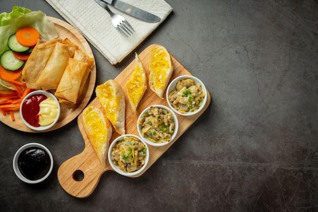 Palourde au four à l'ail et au beurre servie avec du pain à l'ail sur fond sombre