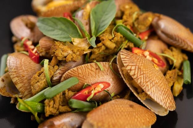 Palourdes frites poudre de curry sur une plaque noire.