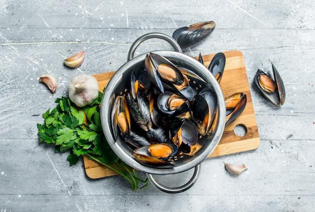 Palourdes de fruits de mer frais avec du persil et de l'ail. sur une table rustique.