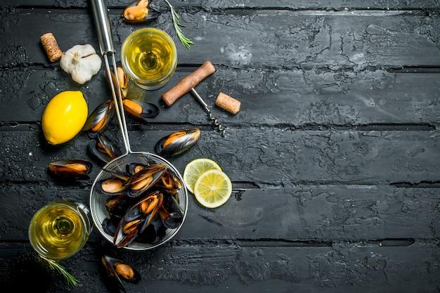 Palourdes de fruits de mer frais avec du vin blanc sur table rustique noire.