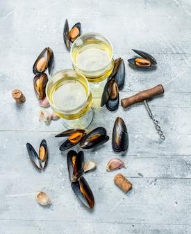 Palourdes de fruits de mer frais avec des verres de vin blanc. sur une table rustique.