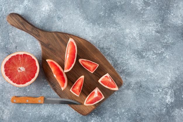 Pamplemousse aigre frais haché placé sur une planche de bois avec un couteau.