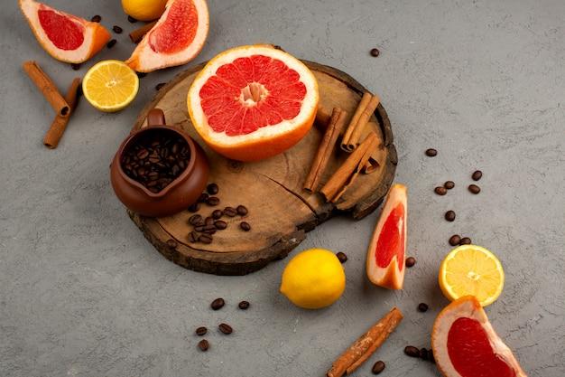 Pamplemousse citron cannelle fruits frais tranchés juteux sur le bureau en bois marron et lumière