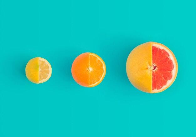 Pamplemousse citron, orange et rouge sur fond bleu clair. concept plat minimal.