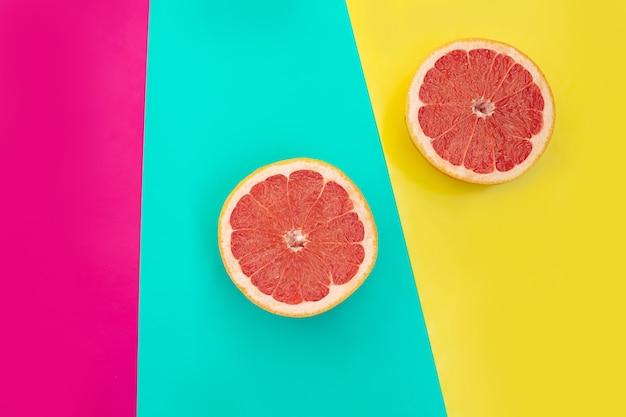 Pamplemousse coupé en deux fruits sur fond jaune et turquoise