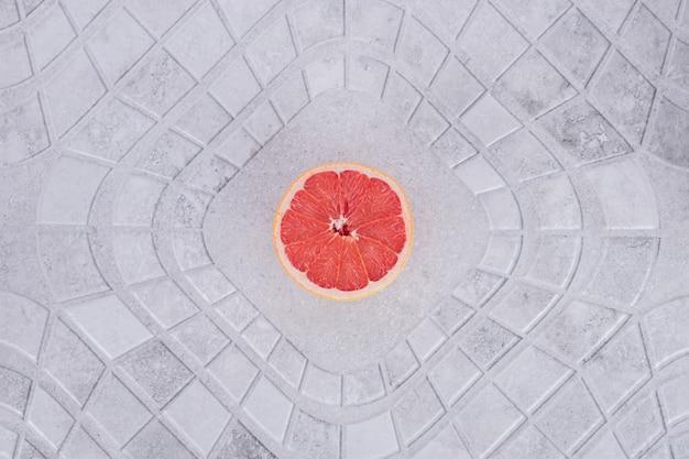 Pamplemousse frais coupé à moitié sur table en marbre.