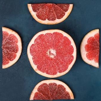 Pamplemousse frais rouge tranché sur bleu.