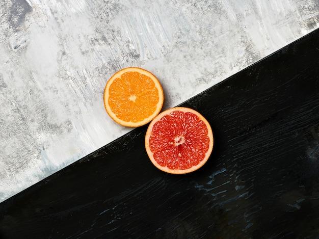 Pamplemousse, mandarine - moitiés d'agrumes sur bois.