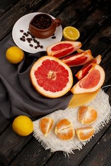 Pamplemousse et mandarines en tranches de citron avec des graines de café sur le rustique en bois brun