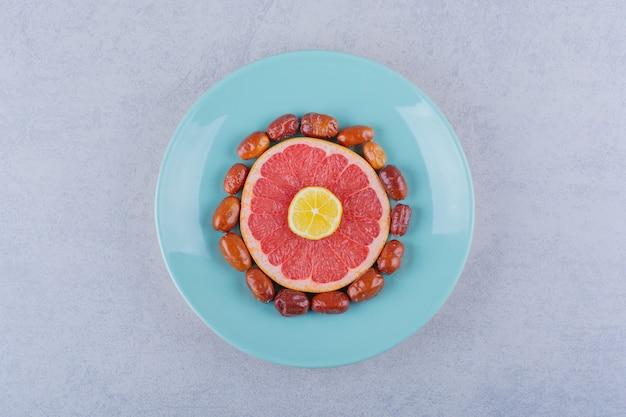 Pamplemousse mûr tranché, citron et baies argentées sur plaque bleue.