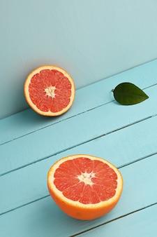 Pamplemousse rouge coupé en deux sur un fond rustique en bois bleu.