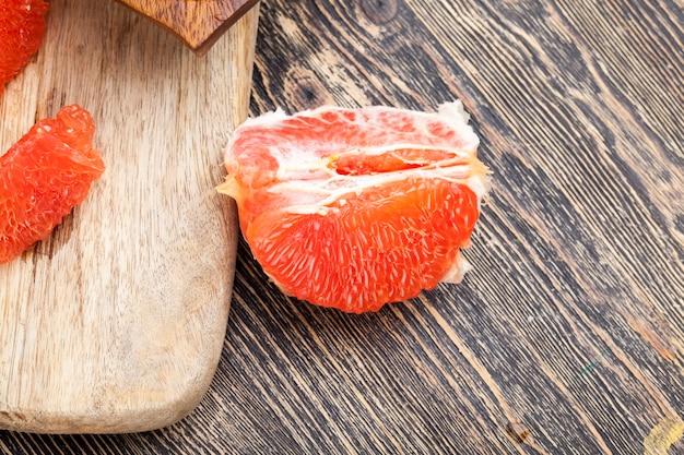 Pamplemousse rouge pelé divisé en tranches pendant la cuisson, pamplemousse d'agrumes juteux