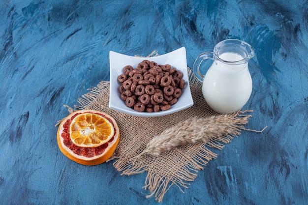 Pamplemousse séché, un bol d'anneaux de maïs et une cruche de lait sur une serviette sur bleu.