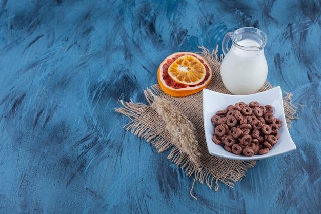 Pamplemousse séché, un bol de rondelles de maïs et une cruche de lait sur une serviette, sur le bleu.