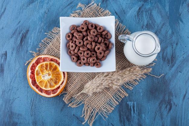 Pamplemousse séché, un bol de rondelles de maïs et une cruche de lait sur une serviette, sur la surface bleue.