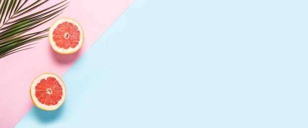 Pamplemousse tranché et branche de palmier sur fond rose et bleu.