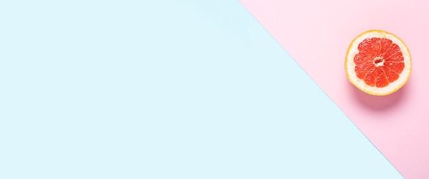 Pamplemousse tranché sur fond rose et bleu.