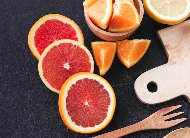 Pamplemousse en tranches mis à côté de l'orange coupée et du citron flou, sur l'arrière-plan