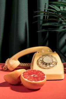 Pamplemousse vue de face à côté de téléphone vintage