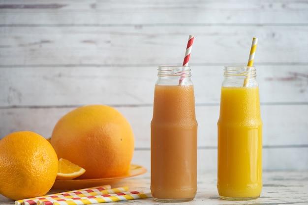 Pamplemousses frais, orange et deux verres de pamplemousse et jus d'orange sur une table en bois clair.