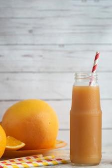 Pamplemousses frais et verre de jus de pamplemousse sur une table en bois clair.