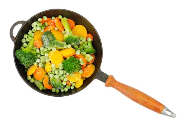 Pan avec des morceaux de légumes surgelés isolés sur une surface blanche