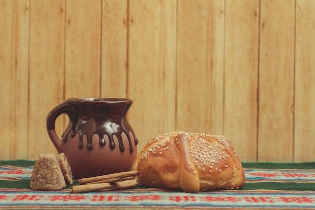 Pan de muerto y taza de chocolate sobre una mesa con mantel tpico mexicano