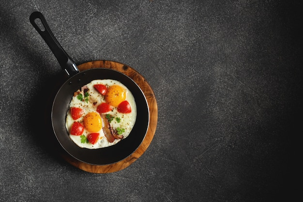 Pan d'oeufs frits, bacon et tomates cerises sur table sombre
