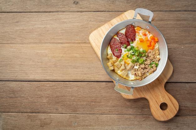 Pan oeufs saupoudrés de saucisse chinoise, bacon en dés, petit déjeuner.
