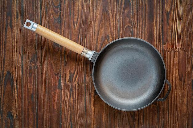 Pan vide sur une table en bois. concept: cuisine, cuisine, vue de dessus